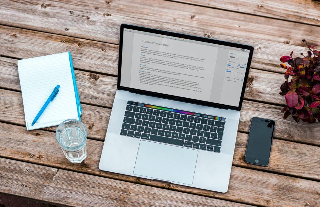 Laptop, zeszyt i woda na biurku